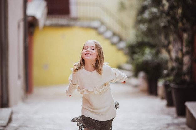 Adorable little girl in trend clothes runing in old town in sunny spring day