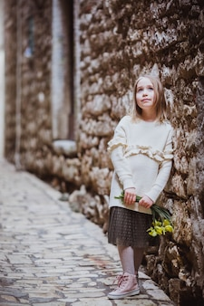 Adorable little girl in trend clothes standing in old town in sunny spring day with yellow flowers