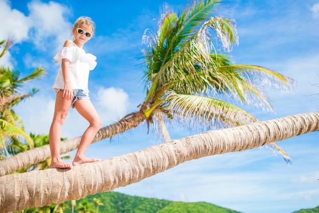 Adorable little girl at tropical beach on palm tree during summer vacation