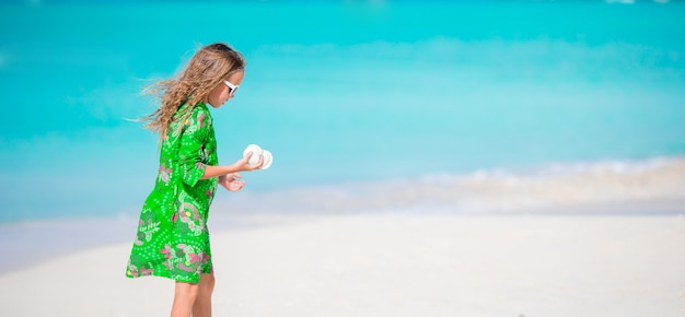 Adorable little girl on tropical beach playing with seashells