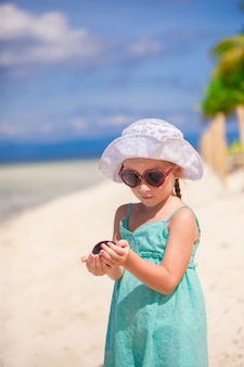 Adorable little girl on tropical beach vacation at phillipines with shell in hand