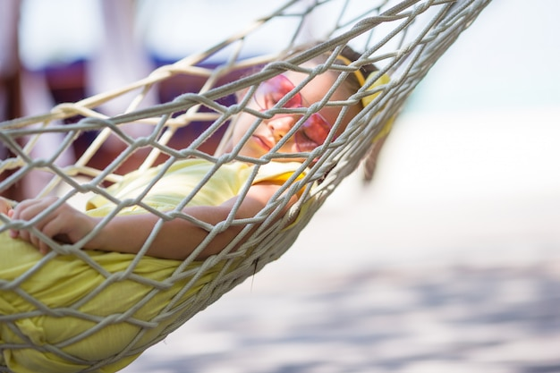 Adorable little girl on tropical vacation relaxing in hammock