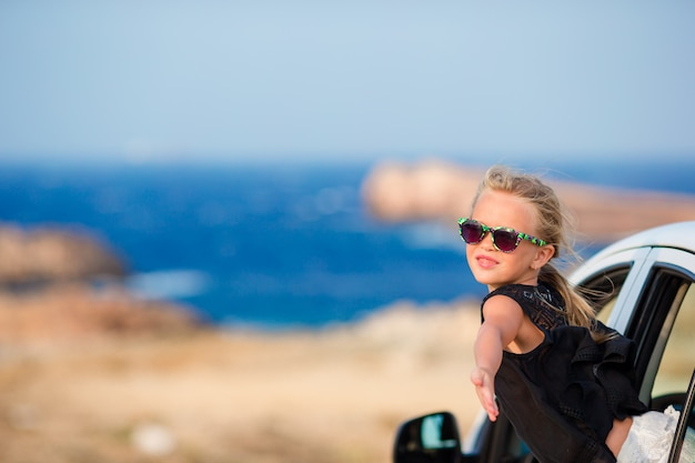 Adorable little girl on vacation travel by car with beautiful landscape
