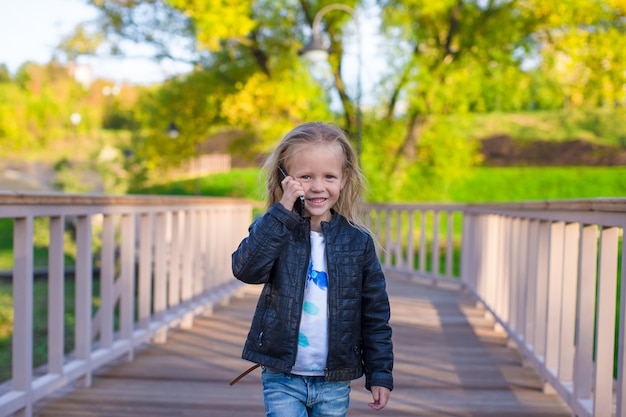 Adorable little girl at warm autumn day outdoors