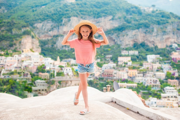 Adorable little girl on warm and sunny summer day in positano town in italy