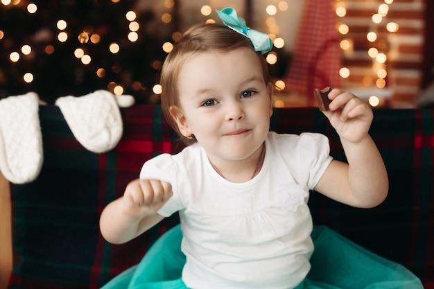 Очаровательная маленькая девочка в белой футболке с бирюзовым бантом на голове