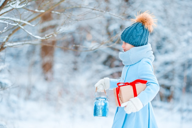 Adorable little girl wearing warm coat outdoors on christmas day holding gift and flashlight