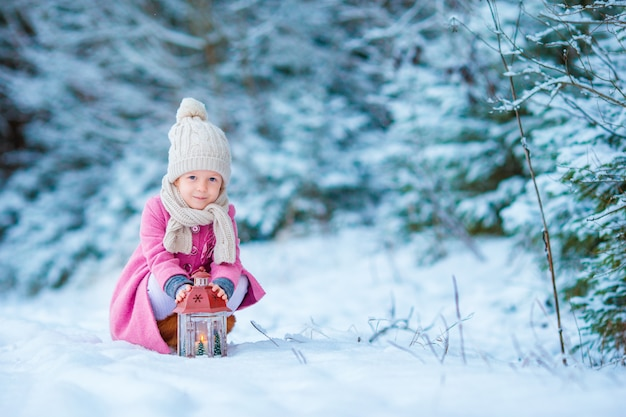 Adorable little girl wearing warm coat outdoors on christmas day warms cold hands by flashlight