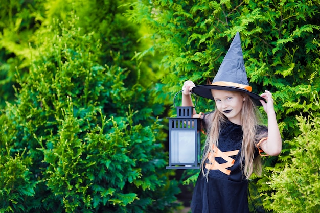Adorable little girl wearing witch costume with broom on halloween outdoors