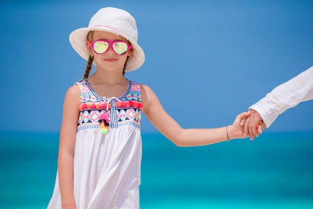 Adorable little girl in white dress at beach during summer vacation