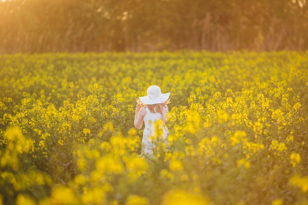 Adorable little girl in white dress and hat is running on spring field of yellow flowers