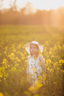 Adorable little girl in white dress and hat on spring field of yellow flowers