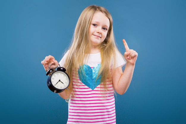 Adorable little girl in white striped shirt with blue heart and jeans hold alarm clock