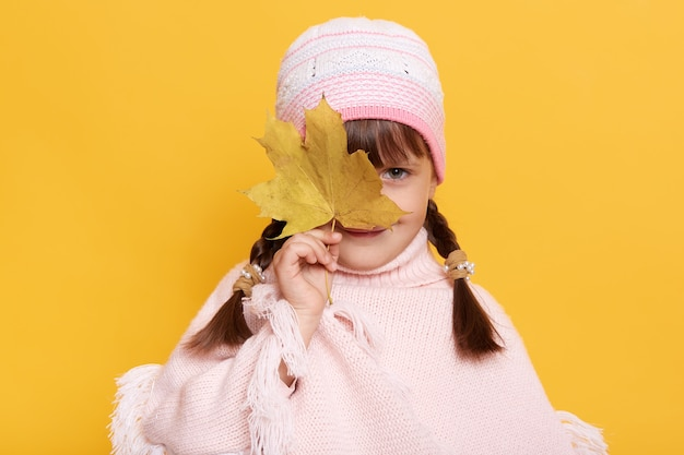 Очаровательная маленькая девочка с осенним листом в руках, прикрывающая глаз листом, смотрящая прямо вперед, в кепке и вязаном пончо