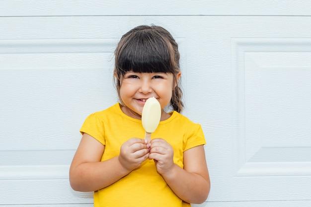 Очаровательная маленькая девочка с черными волосами ест мороженое в желтой рубашке, прислонившись к белому фону