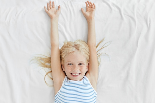Adorable little girl with blonde hair and freckles, waking up in morning, stretching on white bedclothes, having pleasant smile