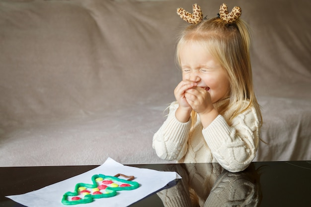Adorable little girl with blonde hair playing with clay and making christmas tree at home