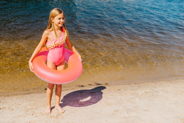 Adorable little girl with bright swim ring on seashore