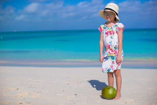 Adorable little girl with coconut at white beach have fun