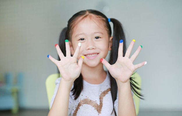 Adorable little girl with colorful fingers painted in the children room.