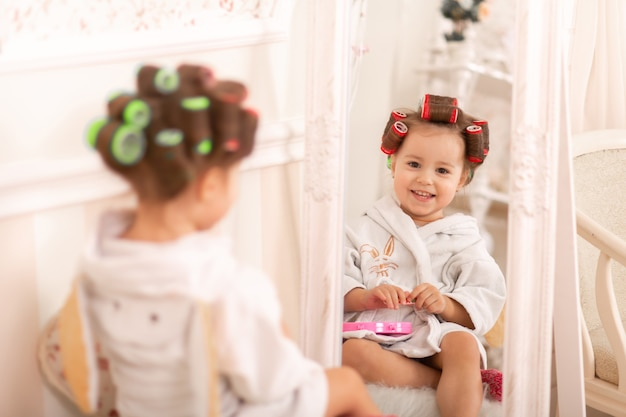 Adorable little girl with curlers paints her fingernails. copies mom's behavior. young fashionista. beauty day.