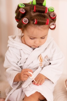 Adorable little girl with curlers paints her fingernails
