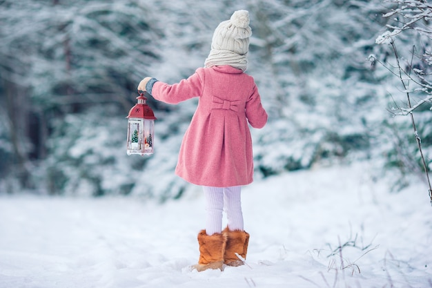 Adorable little girl with flashlight and candle in winter