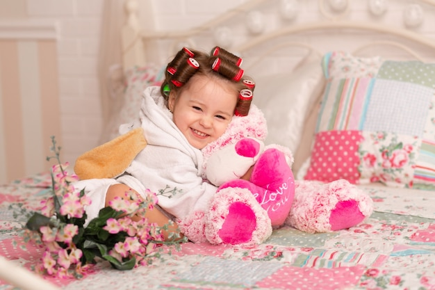 Adorable little girl with hair curlers hugs her favorite teddy bear toy.