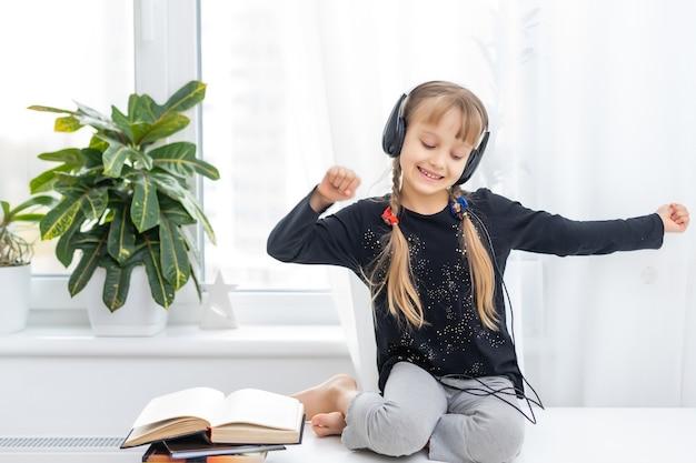 집에 있는 테이블에 헤드폰을 끼고 있는 사랑스러운 어린 소녀