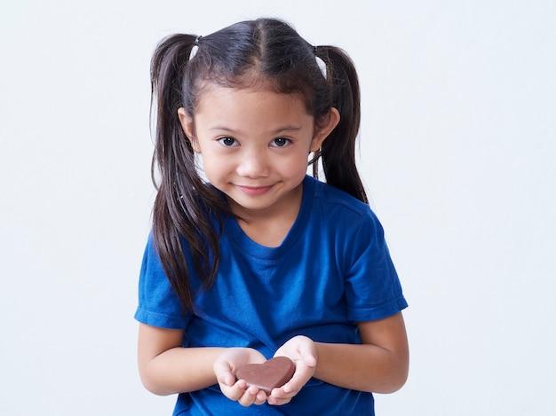 孤立したハート型のチョコレートを持つ愛らしい少女