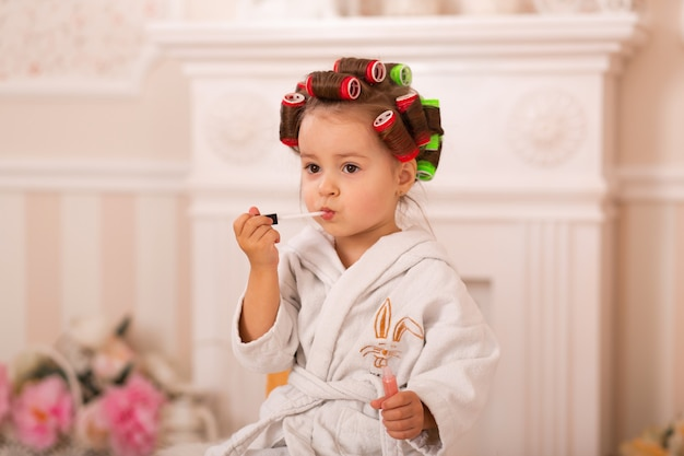 Adorable little girl with her mother in hair curlers apply makeup. mom teaches daughter to use cosmetics. beauty day. girls are such girls.
