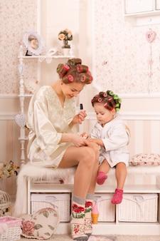 Очаровательная маленькая девочка с матерью в бигуди красят ногти. копирует поведение мамы. мама учит дочь заботиться о себе. день красоты.