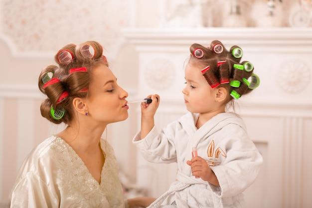 머리카락 curlers에서 그녀의 어머니와 함께 사랑스러운 어린 소녀는 메이크업을 적용합니다. 엄마는 딸에게 화장품을 사용하도록 가르칩니다. 뷰티 데이. 소녀들은 그런 소녀들입니다.
