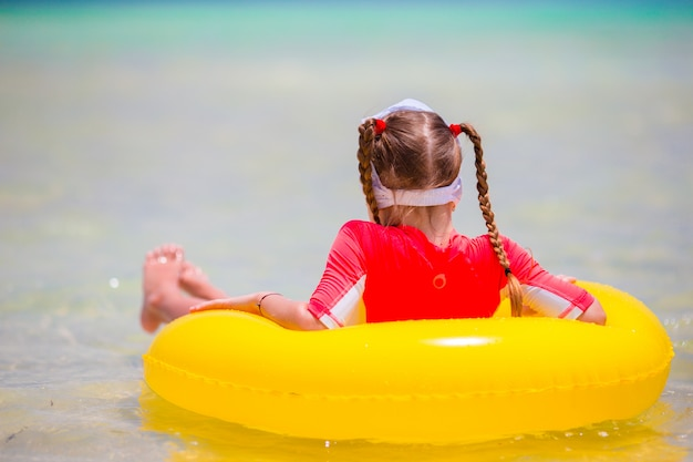 Adorable little girl with inflatable rubber circle during beach vacation. kid having fun on summer active vacation