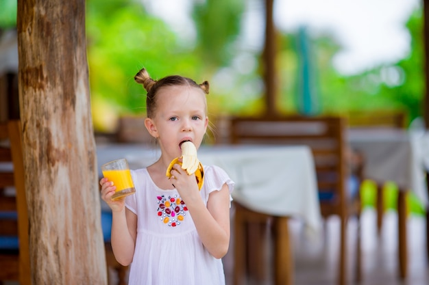 Adorable little girl with juice and banana at outdoor cafe