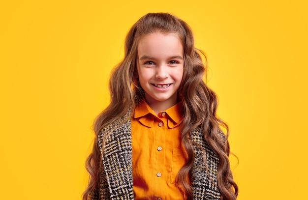 オレンジ色のシャツの上にカジュアルな市松模様のコートを着て笑顔と探している長いウェーブのかかった髪の愛らしい少女