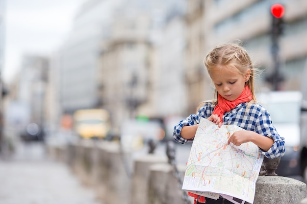 Adorable little girl with map of european city outdoors