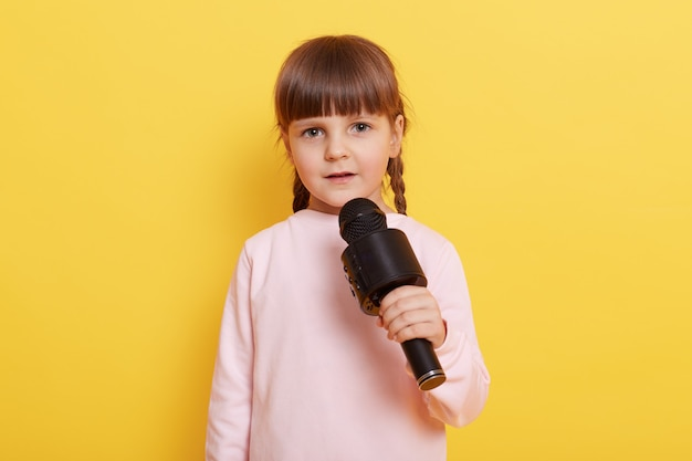 Adorable little girl with microphone on yellow background, looks at camera while talking in mic, pointing index finger aside. copy pace for advertisement or promotional text.
