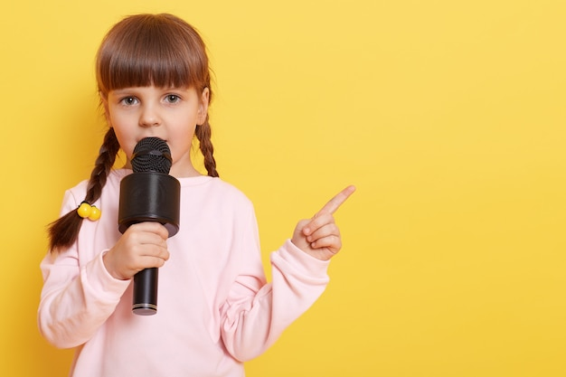 Adorable little girl with microphone on yellow wall, while talking in mic, pointing index finger aside. copy pace .