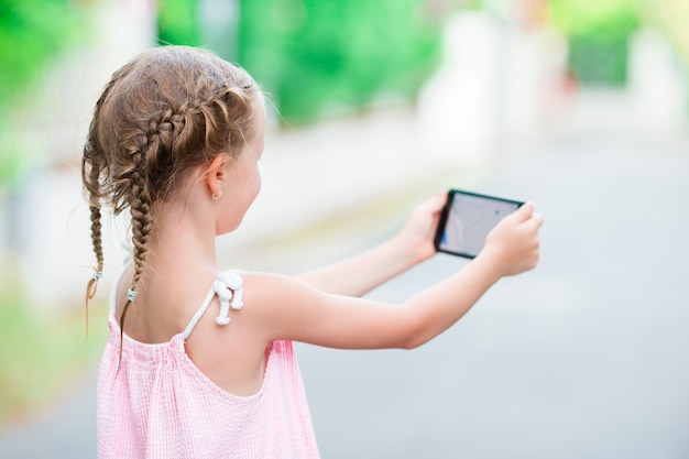 Adorable little girl with phone during summer vacation outdoors