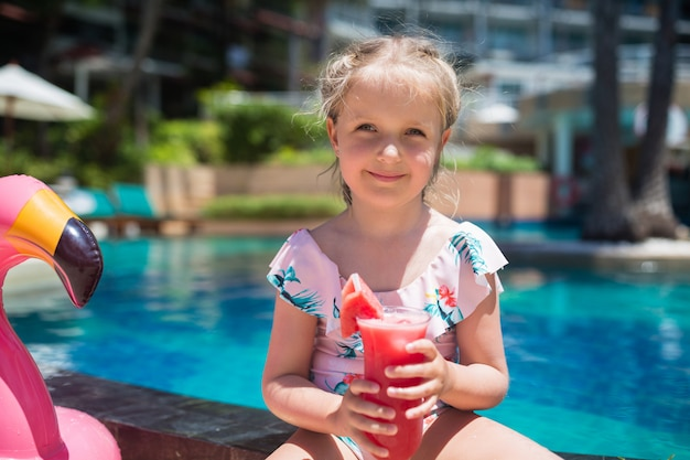 Adorable little girl with pink flamingo inflatable ring drinking fresh watermelon juice