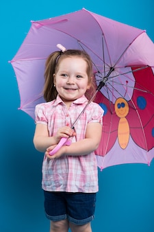 Adorable little girl with pink umbrella on blue background