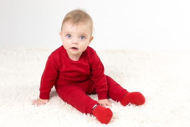 Очаровательная маленькая девочка с красной пиямой на белом фоне