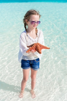 Adorable little girl with starfish on the beach