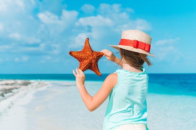 Очаровательная маленькая девочка с морскими звездами на белом пустом пляже