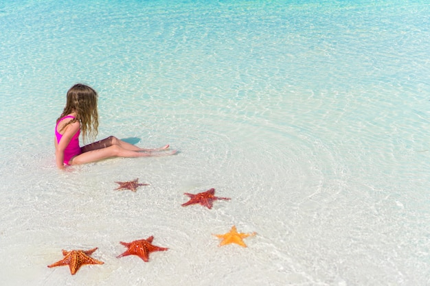 Adorable little girl with starfishes in water on white empty beach