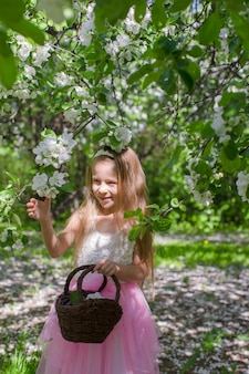 Adorable little girl with straw basket in blossoming apple garden