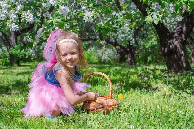 Adorable little girl with straw basket in blossoming apple orchard
