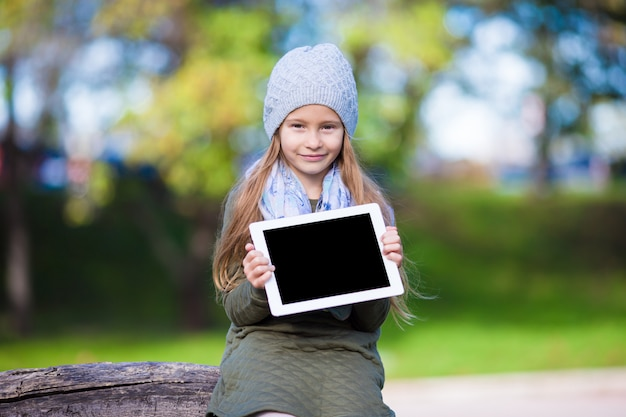 Adorable little girl with tablet pc outdoors in autumn sunny day