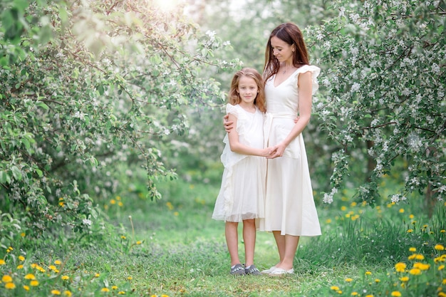 Adorable little girl with young mother in blooming cherry garden on beautiful spring day